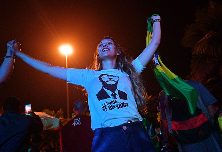 A supporter of presidential candidate for the Social Liberal Party (PSL) Jair Bolsonaro, Soraya Nardelli, 23, celebrates outside of the residential condominium where he lives after the first round of general elections, in Barra da Tijuca, in Rio de Janeiro, Brazil.