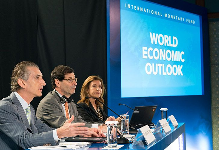 This handout photo taken and released by the International Monetary Fund on October 9, 2018 shows IMF Economic Counsellor Maurice Obstfeld (centre), deputy director Gian Maria Milesi-Ferretti (left) and communications officer Wafa Amr (right) answering questions during the World Economic Outlook press conference.