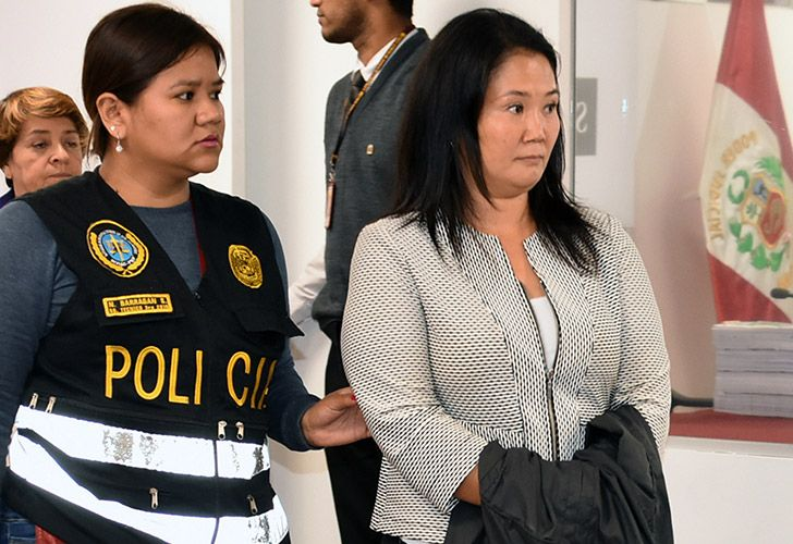 Handout picture distributed by Peruvian Judiciary showing Keiko Fujimori, opposition leader and daughter of disgraced ex-president Alberto Fujimori, being escorted by police officers in a Judiciary office, in Lima, following her arrest on October 10, 2018, for alleged money laundering involving Brazilian construction giant Odebrecht.
