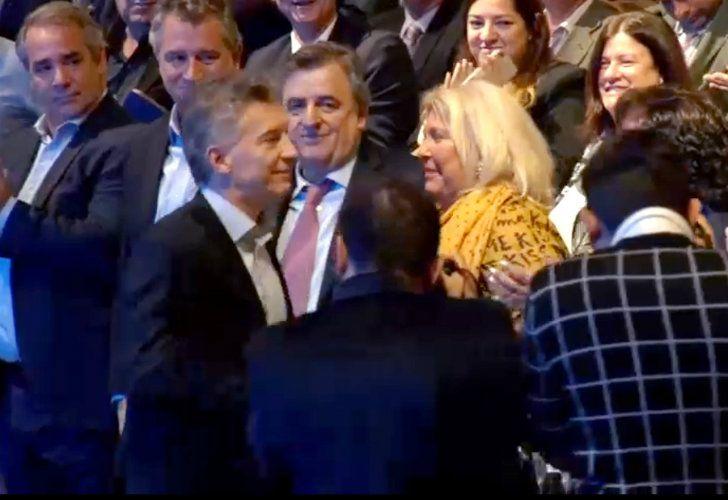 Macri and Carrio and an awkward salute.