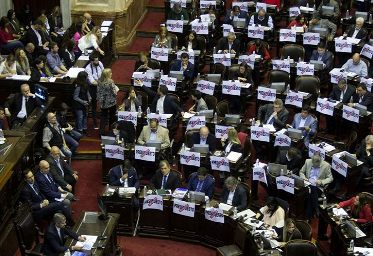 Members of Argentina's Lower House sit behind signs against the 2019 Budget.