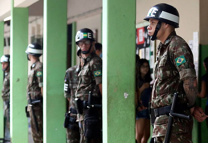 Brazilian soldiers stand guard as people wait in line to cast their votes at the polling centre in Rio de Janeiro, Brazil October 28, 2018 Brazilians will choose their president today during the second round national election between the far-right firebrand Jair Bolsonaro and leftist Fernando Haddad.