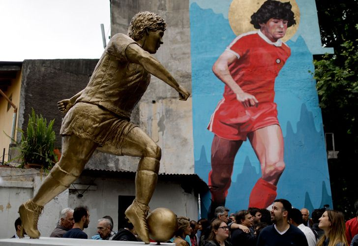 People stand beside statue of Diego Maradona, during its presentation in Buenos Aires. The statue by artist Jorge Martínez was unveiled Wednesday to honour Maradona on his 58th birthday (which was on Tuesday).