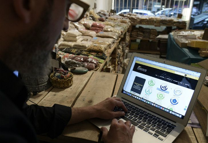 Businessman Fernando Hechtlinger uses his laptop at his natural foods grocery store in Buenos Aires.
