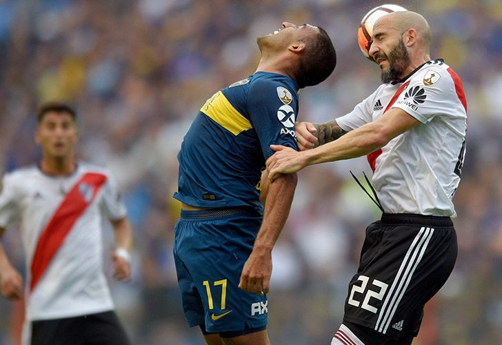 Ramón Ábila of Boca Juniors, centre, challenges for the ball with Javier Pinola of River Plate during the first leg of the Copa Libertadores final at the Bombonera.