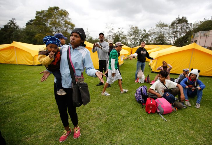 Venezuelan migrants speak to the press as they arrive to a new, refugee-style camp set up by the government in Bogotá.