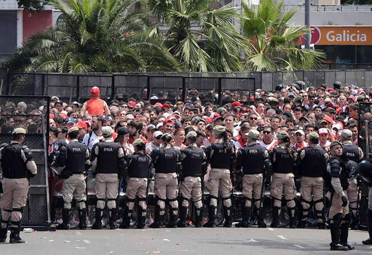 Security forces stand guard outside outside the Monumental, where River Plate fans gather before the announcement that their team's final Copa Libertadores match against rival Boca Juniors was to be suspended for a second day in a row.