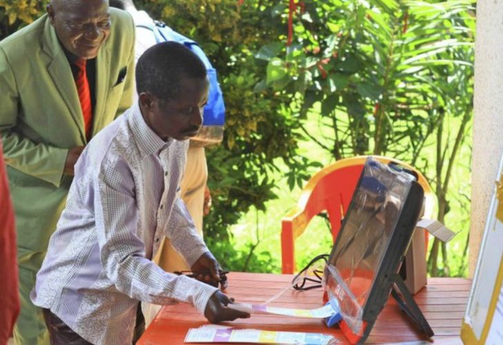A Congolese citizen places his vote in an electronic voting machine.