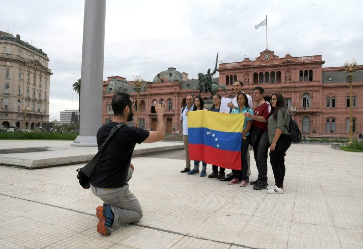 Venezuelans who now live in Argentina pose with a flag of their country outside the Casa Rosada.