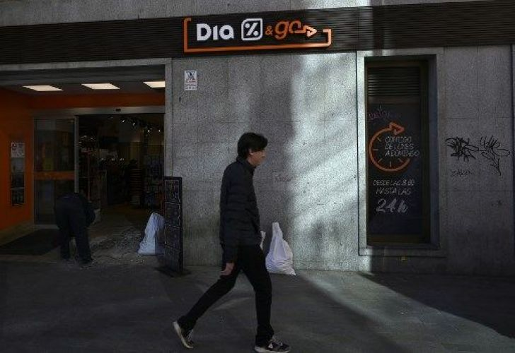Pedestrians pass by a Dia storefront in Madrid.