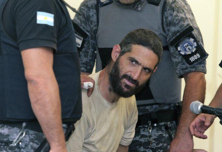 Nicolás Gil Pereg is taken by police officers into custody.