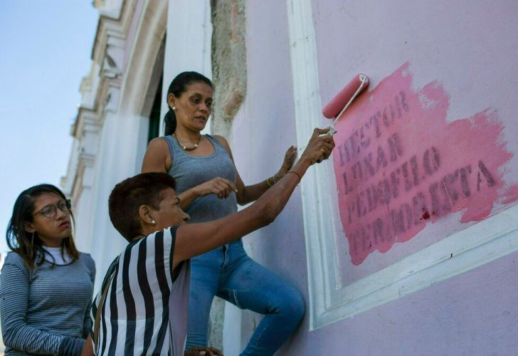 """In this Feb. 9, 2019 photo, faithful paint over graffiti that reads in Spanish: """"HECTOR LUNAR, PEDOPHILE, TERRORIST,"""" on a wall of the Dulce Nombre de Jesus church, in the Petare slum of Caracas, Venezuela."""