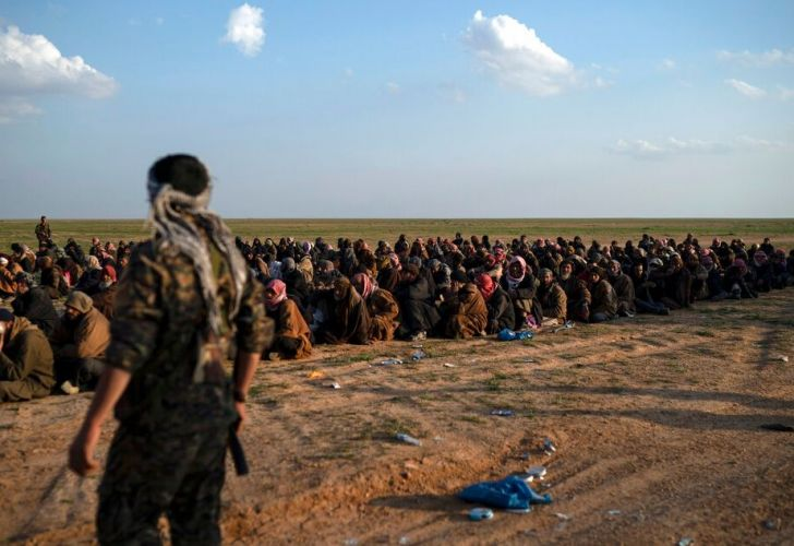 U.S.-backed Syrian Democratic Forces (SDF) fighters stand guard next to men waiting to be screened after being evacuated out of the last territory held by Islamic State group militants.
