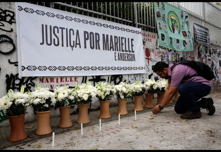 During a presentation marking the one year anniversary of the death of Rio Councilwoman Marielle Franco, in Rio de Janeiro, Brazil, a man lights a candle in front of a row of flowers to commemorate her death.