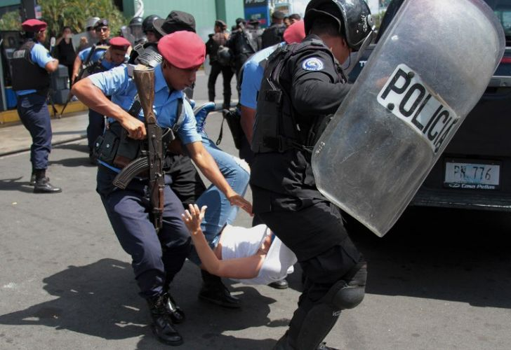 Nicaraguan riot police officers detain a protester during a demonstration led by opposition groups to demand the release of those arrested for taking part in anti-government protests.