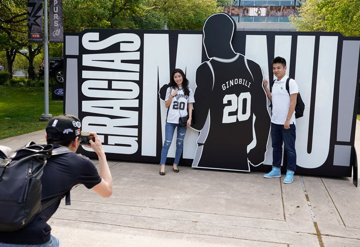San Antonio Spurs fans pose for a photo in front of a sign thanking Manu Ginóbili before an NBA basketball game against the Cleveland Cavaliers on Thursday.