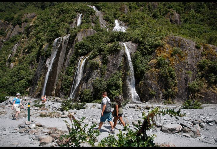 Tourists walk by waterfalls at the Franz Josef Glacier in New Zealand in February of 2016. The Fox and Franz Josef glaciers have been melting so rapidly in recent years that it has become to dangerous for tourists to hike onto them from the valley floor.