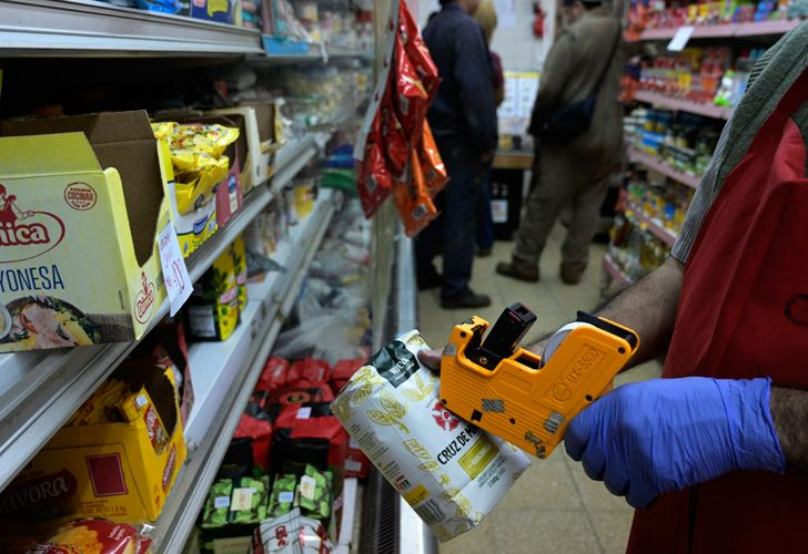 A supermarket worker prices up a bag of yerba mate in a small store in Buenos Aires City.
