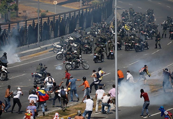 Opponents to Venezuela's President Nicolás Maduro confront loyalist Bolivarian National Guard troops firing tear gas at them, outside the La Carlota military airbase in Caracas.