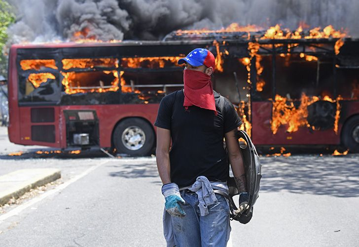 An opposition demonstrator walks near a bus in flames during clashes with soldiers loyal to Venezuelan President Nicolás Maduro, after some troops joined opposition leader Juan Guaidó in his campaign to oust Maduro's government, in the surroundings of La Carlota military base in Caracas on April 30, 2019.
