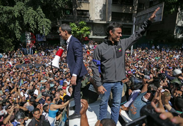 Venezuelan opposition leader and self-proclaimed interm president Juan Guaidó (left) and high-profile opposition politician Leopoldo López greet supporters in Caracas.
