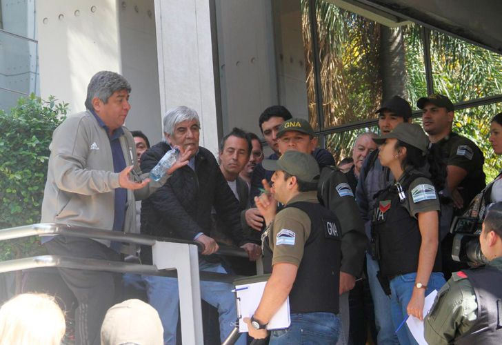 Officials from the Camioneros union (including Hugo Moyano) argue with Gendarmerie officers outside the labour group's headquarters.