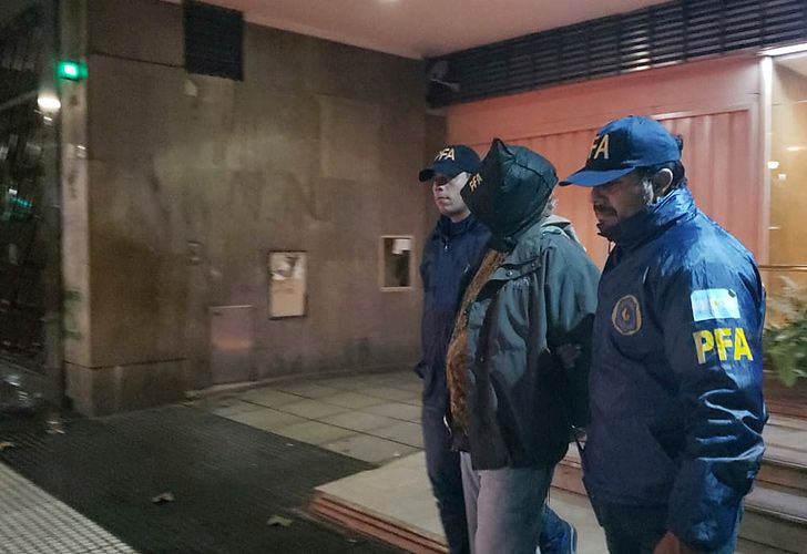 In this handout released by the Policía Federal Argentina, police escort an unidentified man, one of at least four people who have detained in the shooting attack that seriously wounded a lawmaker and killed a provincial official, in Buenos Aires, Argentina, Thursday, May 9, 2019.